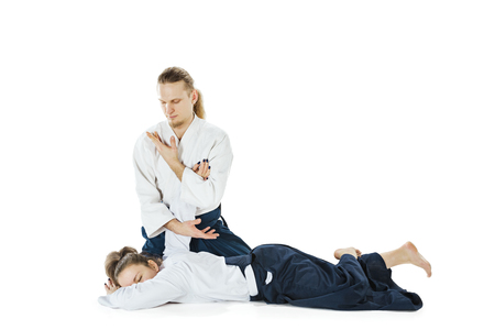 Man and woman fighting at Aikido training in martial arts school