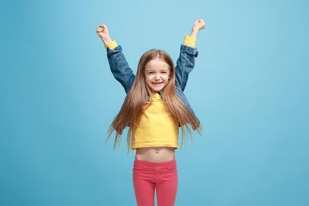 Happy success teen girl celebrating being a winner. Dynamic energetic image of female model