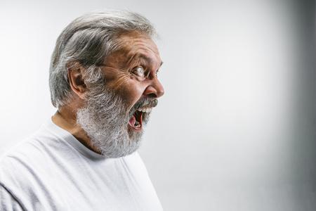 Starszy emocjonalny zły mężczyzna krzyczy na białym tle studia