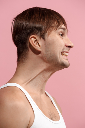 Handsome man looking suprised isolated on pink
