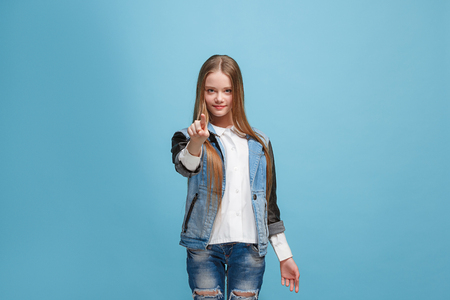 The happy teen girl pointing to you, half length closeup portrait on blue background.