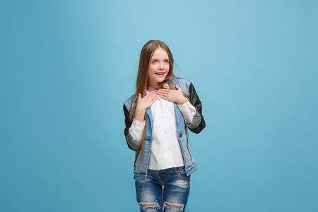 The happy teen girl standing and smiling against pink background.