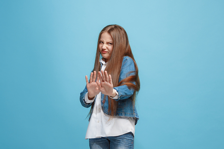 Doubtful pensive teen girl rejecting something against blue background