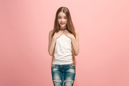 Beautiful teen girl looking suprised isolated on pink