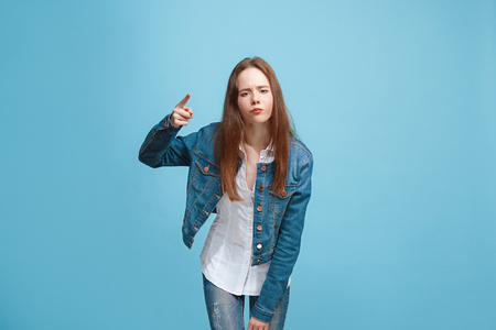 Beautiful female half-length portrait on blue studio backgroud. The young emotional teen girl Stok Fotoğraf - 99954891