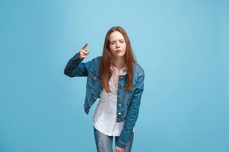 Beautiful female half-length portrait on blue studio backgroud. The young emotional teen girl