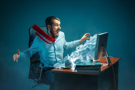 De jonge beklemtoonde knappe zakenman die bij bureau in modern bureau werken die bij laptop het scherm schreeuwen en boos zijn over spam
