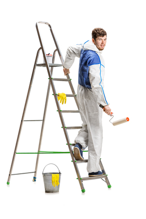 Young male decorator painting with a paint roller climbed a ladder isolated on white background. Stock fotó - 99950327