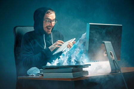Young stressed handsome businessman working at desk in modern office shouting at laptop screen and being angry about spam Stock Photo