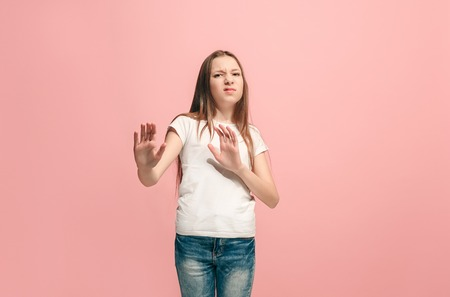 Doubtful pensive teen girl rejecting something against pink background
