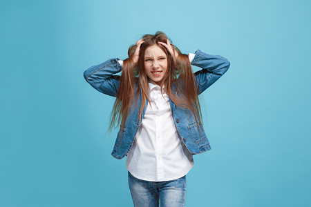 The squint eyed teen girl with weird expression isolated on blue Stok Fotoğraf