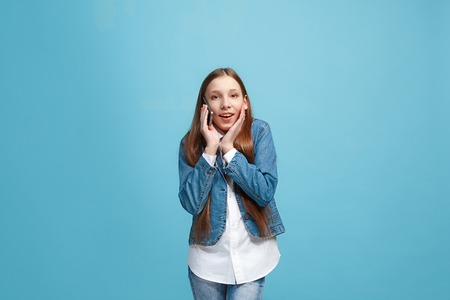 Beautiful teen girl looking suprised isolated on blue Stock Photo