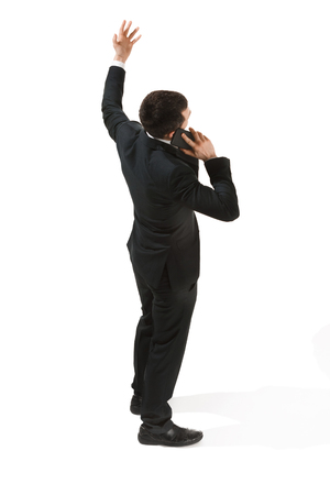 Back view portrait of a businessman. Confident professional with mobile phone Stock Photo