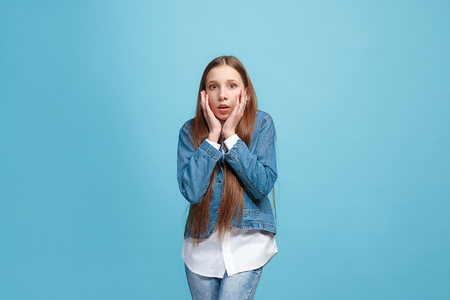 Wow. Beautiful female half-length front portrait isolated on blue studio backgroud. Young emotional surprised teen girl standing with open mouth. Human emotions, facial expression concept. Trendy colors Stock Photo