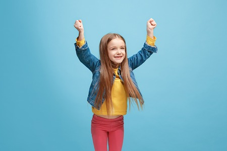 I won. Winning success happy teen girl celebrating being a winner. Dynamic image of caucasian female model on blue studio background. Victory, delight concept. Human facial emotions concept. Trendy colors