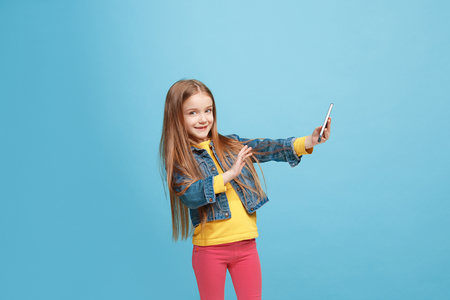 The happy teen girl standing and smiling against blue background.