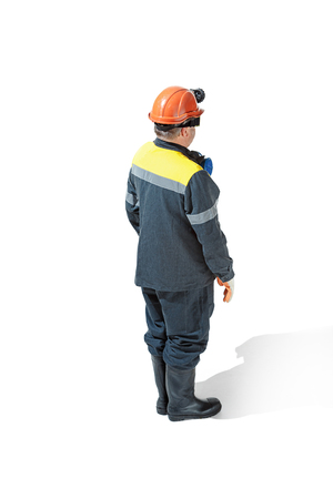 The studio shot of senior bearded male miner standing at the camera on a white background.