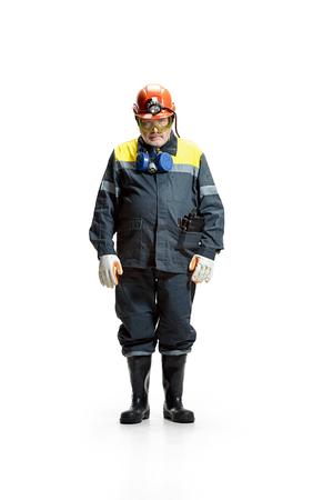 The studio shot of sad senior bearded male miner standing at the camera on a white background. 版權商用圖片
