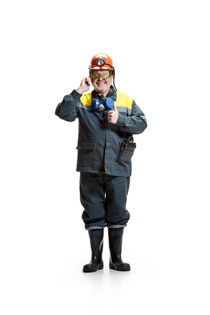 The studio shot of happy senior bearded male miner standing at the camera with smartphone on a white background. 版權商用圖片