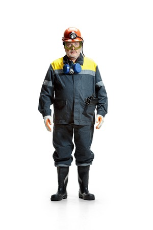 The studio shot of serious senior bearded male miner standing at the camera on a white background. Stock Photo