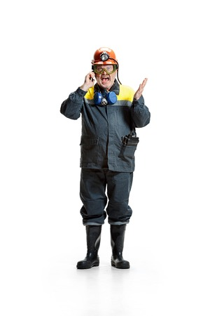 The studio shot of angry senior bearded male miner standing at the camera with smartphone on a white background. Stock Photo