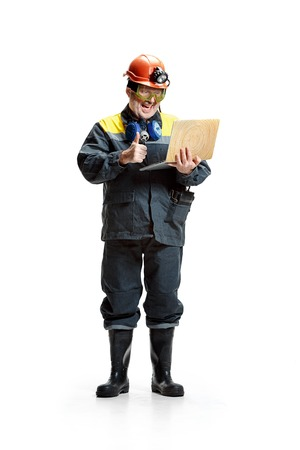 The studio shot of happy senior bearded male miner standing at the camera with laptop on a white background.
