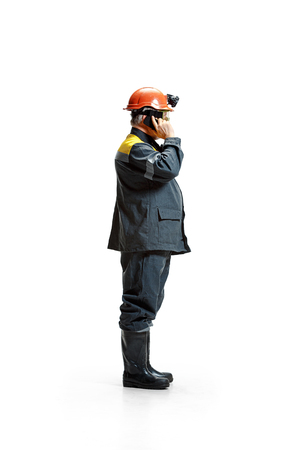 The studio shot of serious senior bearded male miner standing in profile view at the camera with smartphone on a white background.