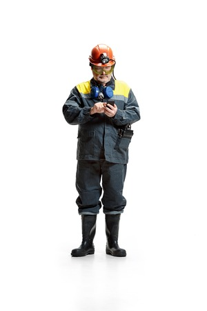 The studio shot of serious senior bearded male miner standing at the camera with smartphone on a white background.