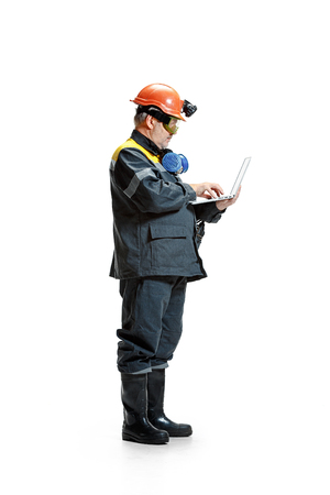 The studio shot of serious senior bearded male miner standing in profile view at the camera with laptop on a white background.