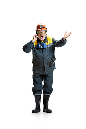 The studio shot of surprised senior bearded male miner standing at the camera with smartphone on a white background.