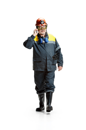 The studio shot of serious senior bearded male miner in motion at the camera with smartphone on a white background. Stock Photo