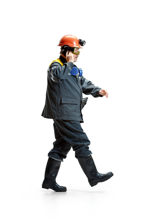 The studio shot of serious senior bearded male miner in motion at the camera with smartphone on a white background. 版權商用圖片