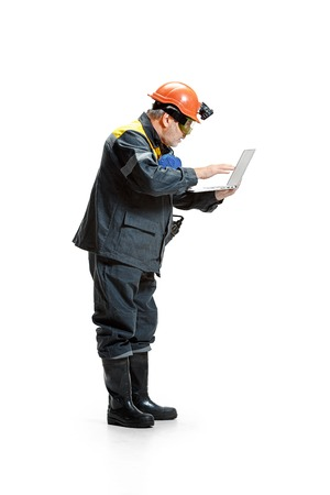 The studio shot of pensive senior bearded male miner standing in profile view at the camera with laptop on a white background. 版權商用圖片
