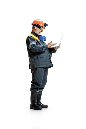 The studio shot of happy senior bearded male miner standing in profile view at the camera with laptop on a white background. 版權商用圖片