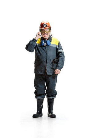 The studio shot of angry senior bearded male miner standing at the camera with smartphone on a white background. 版權商用圖片