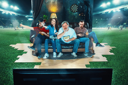 Ardent fans are sitting on the sofa and watching TV in the middle of a football field. Stock Photo