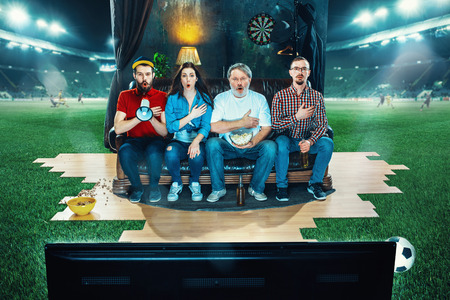 Ardent fans are sitting on the sofa and watching TV in the middle of a football field. Archivio Fotografico