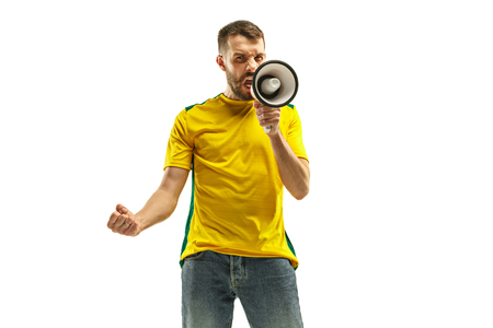 Brazilian fan celebrating on white background. The young man in soccer football uniform with megaphone at white studio. Fan, support, win, winner concept. Human emotions concepts.