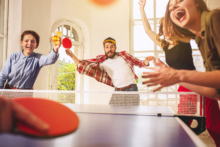 Gruppo di giovani amici felici giocando a ping pong ping pong Archivio Fotografico