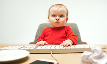 Happy child baby girl toddler sitting with keyboard of computer isolated on a white background Фото со стока