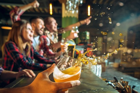 sport, people, leisure, friendship and entertainment concept - happy football fans or male friends drinking beer and celebrating victory at bar or pub Stockfoto