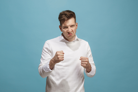 The young emotional angry man screaming on studio background Stock Photo