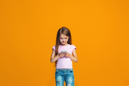 The happy teen girl standing and smiling with phone