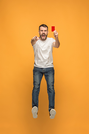 Football supporter with red card on orange background