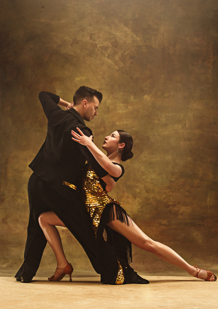 Dance ballroom couple in gold dress dancing on studio background. Stock Photo