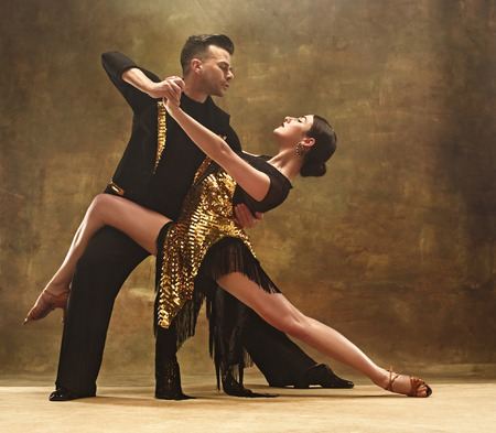 Dance ballroom couple in gold dress dancing on studio background. Banque d'images
