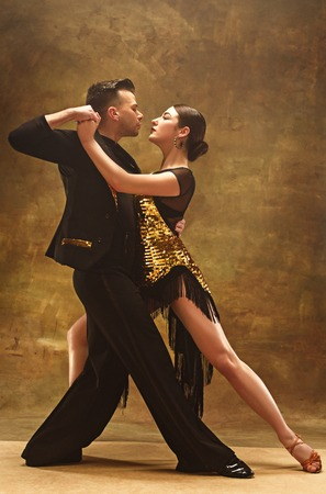 Dance ballroom couple in gold dress dancing on studio background. Foto de archivo