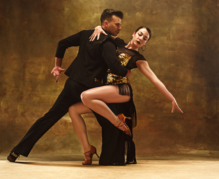 Dance ballroom couple in gold dress dancing on studio background. Stockfoto