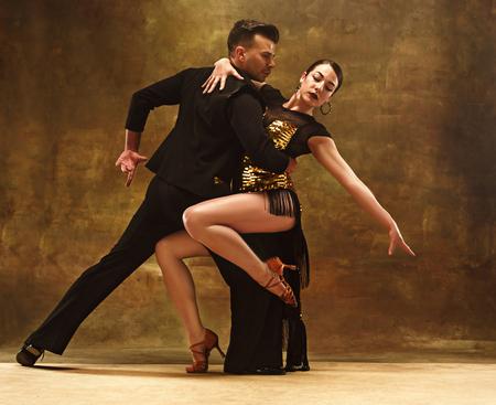 Tanzballsaalpaar im Goldkleid, das auf Studiohintergrund tanzt.
