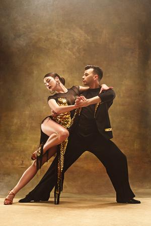 Dance ballroom couple in gold dress dancing on studio background. Stock Photo